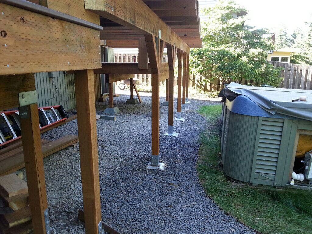 Post anchors and base plates supporting a deck built without digging holes.